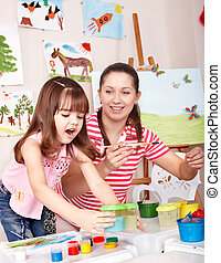 Child painting with teacher in preschool. - Little girl...