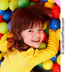 Little girl with group ball Play room