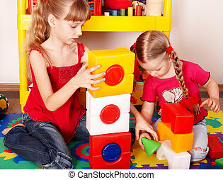 Child with puzzle, block and construction set in play room...