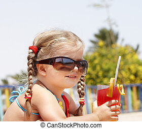 Child drinking orange juice. - Little girl in glasses and...