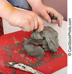 Child molding from clay in play room. Body part.
