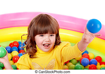 Little girl play in group colourful ball.