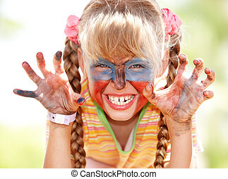 Child girl with paint on face.