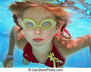 Child girl swim underwater in pool.