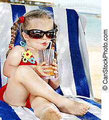 Child in glasses and red bikini drink juice - Little girl in...