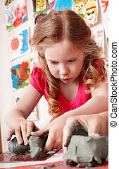 Child molds clay in play room Preschool