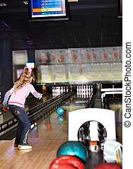 Child girl in with bowling ball learn game