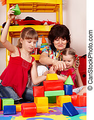Children with block and senior woman in play room....