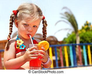 Child girl in glasses and red bikini drink juice.