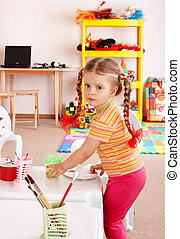 Child with paint and brush in playroom.