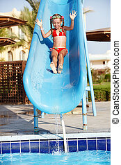 Girl sliding down water slide. Summer.