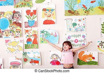 Child with hand up and picture  in playroom. Preschool.