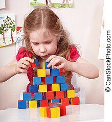 Child preschooler play wood block in play room - Little girl...