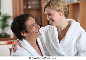 Woman sitting on man's lap, both wearing bathrobes