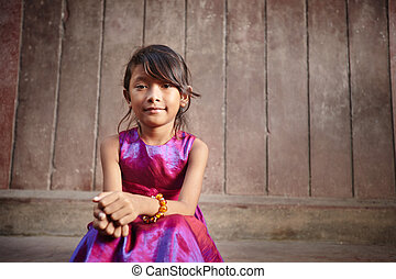 Cute and happy little Asian girl smiling at camera -...
