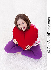Young girl with large red heart pillow