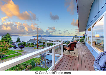 Large balcony of blue house with chairs and water view.