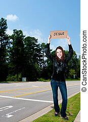 Woman Holding Jesus Sign - A beautiful young woman holding...