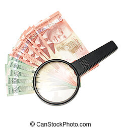 Money Search - A magnifying glass on top of spread out...