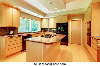 Large kitchen with honey wood and black appliances.