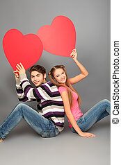 hearts up - Happy young love couple posing together with red...