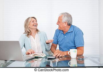 Couple At Dining Table Working on Laptop - Happy couple at...