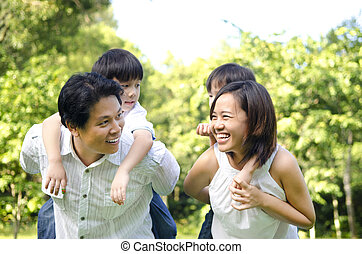Happy Asian family having fun in a nice summer day