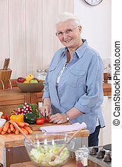 Older woman chopping vegetables