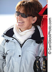 a smiling mature woman in a winter sports resort