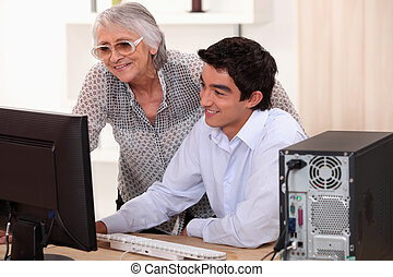 Young man helping his grandma with her computer