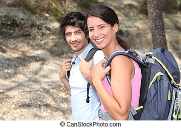 Two backpackers hiking through the forest