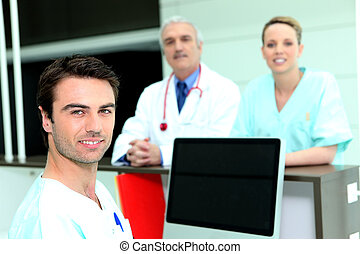 Doctor and nurses around a computer with a blank screen