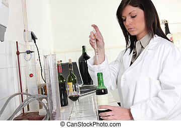 woman in laboratory with bottle of wine and pipette