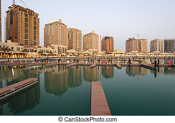 Residential buildings and empty Marina at The Pearl in Doha,...