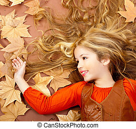 autumn fall little blond girl on dried tree leaves...