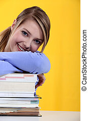 student leaning on a pile of books
