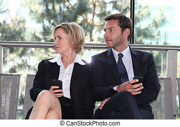 Business executives sitting on a bench texting