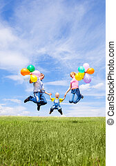 happy family - happy jumping family with balloons outdoor on...