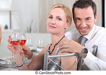 Couple with rose wine at a dinner party