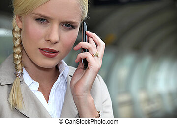 Businesswoman on the phone at a train station