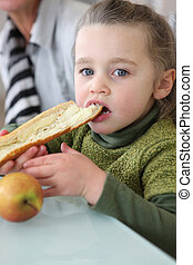 Girl eating slice of buttered bread