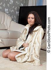 woman  in fur coat  at home interior