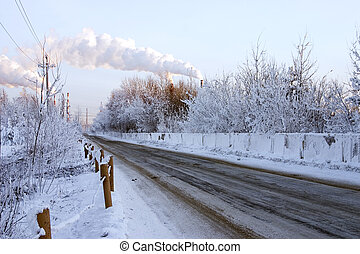 Snow-covered road to an environment of trees with smoking pipes on a background