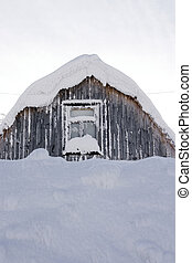 roof and window of a wooden small house covered with snow in the cold winter afternoon