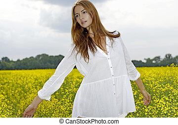 Beautiful woman in a yellow flowers field