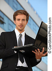 Man in suit carrying a laptop