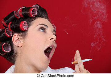 Woman wearing hair-rollers smoking