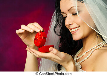 brunette bride looking at the wedding ring