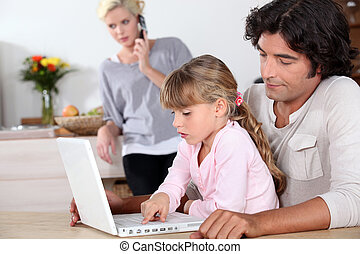 father and her daughter doing computer, mother at phone