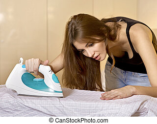 young woman ironing on ironing board - young brunette woman...